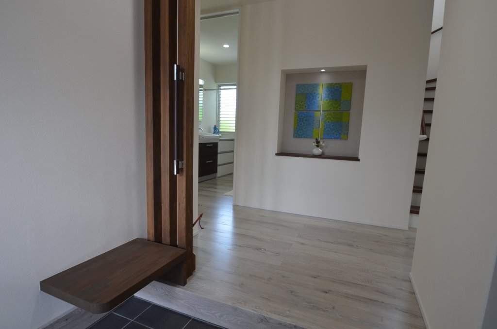 お家の顔である玄関。大きなニッチに飾られたファブリックパネルがお出迎えします。パブリックスペースですので、手すりや腰掛台などの配慮も忘れません。