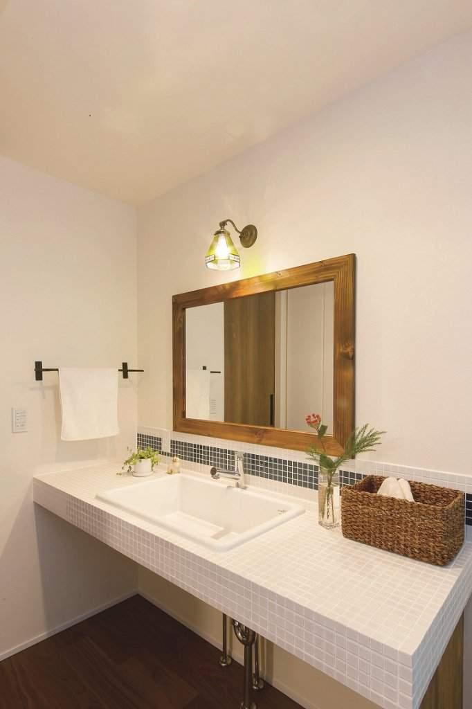 ご夫婦自らタイルを張ったシンプルな洗面台。「下部をオープンにしたのは、使い勝手の良い収納家具を手づくりしたいからです」(奥様)。
