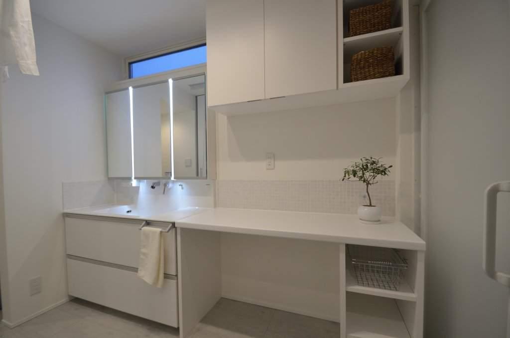 洗面脱衣室は白を基調に清潔感のある空間に。既製品の洗面台+オーダーカウンター、充実の収納、家事室としても大活躍。
