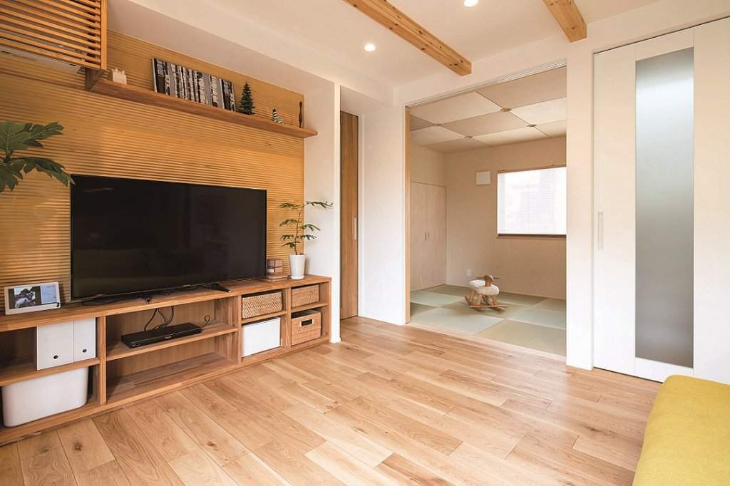 ナラ材の造作家具によりテレビ回りも常に整う。「和室は扉を閉めれば独立します。い草の畳を使い、仏壇や神棚のスペースも設けました」(ご主人)。