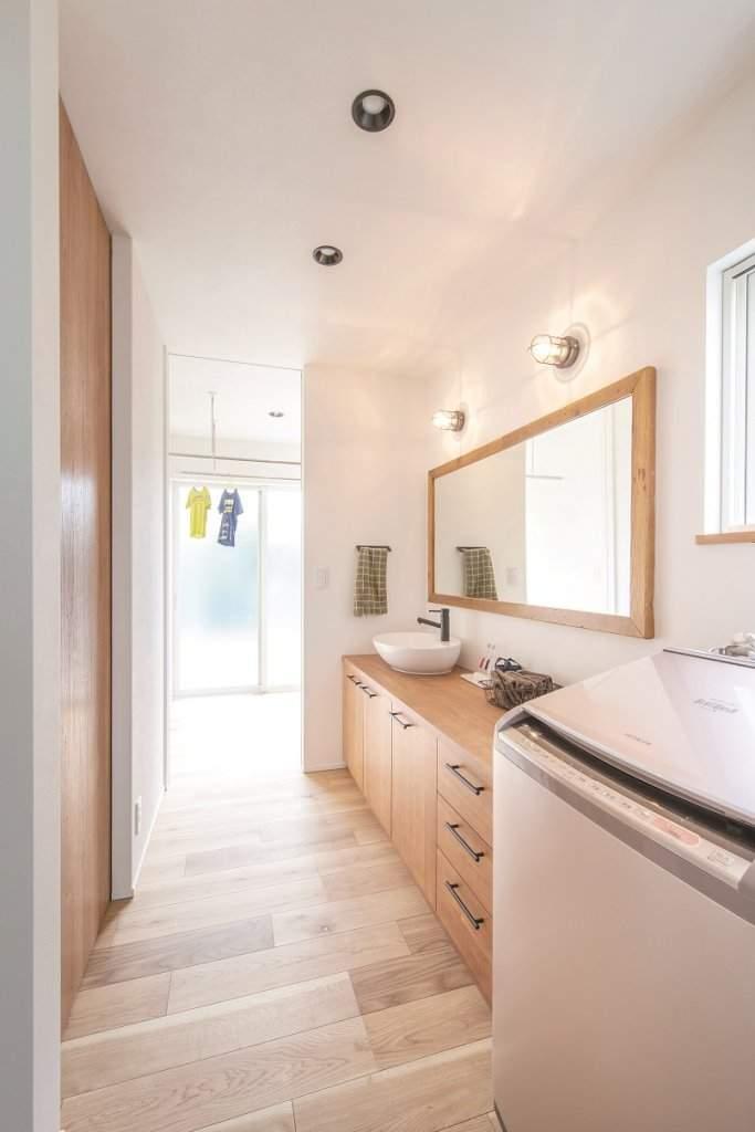 サンルームを隣接させた洗面脱衣室。造作家具と幅160センチのワイドな鏡を備え、忙しい朝も渋滞知らず。