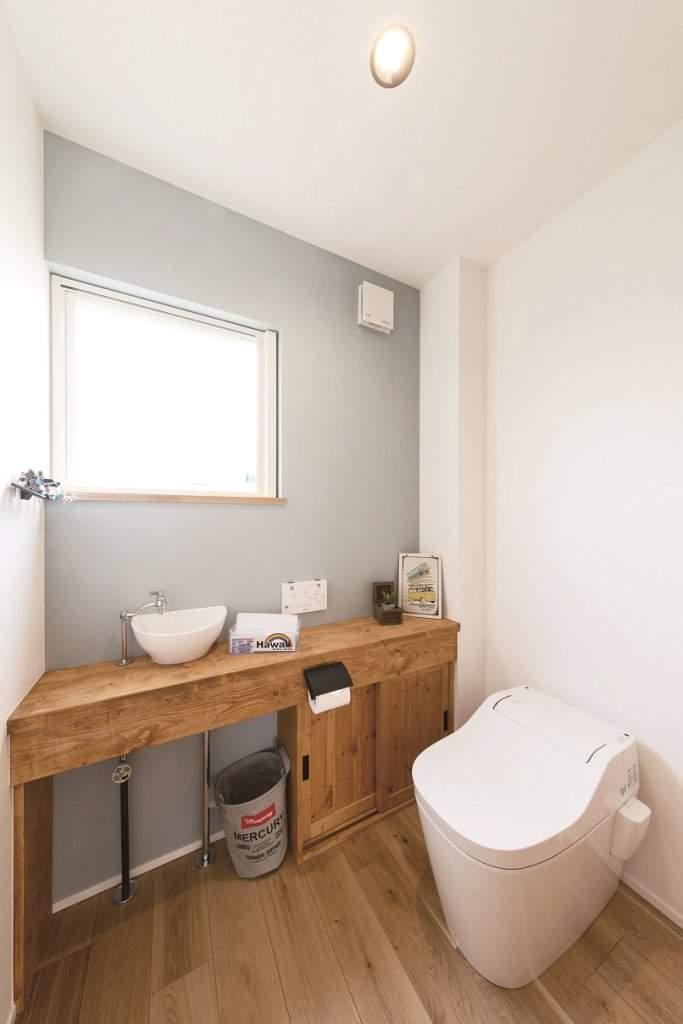 淡いブルーのクロスが爽やかなトイレ。造作家具は木材にエイジング加工を施し、ヴィンテージ感を出した。