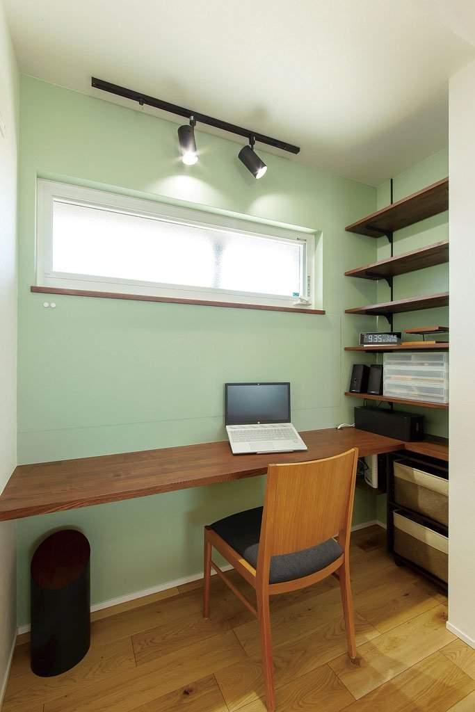 リビングの一角に設けたカウンターデスクと造作の書棚。グリーンの壁紙を張り、爽やかな印象に仕上げた。