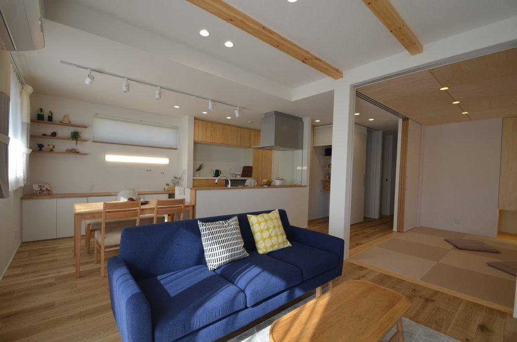 空間を見渡せるすっきりとしたオープンなキッチン、戸を開け放してLDKの一部として広々使える和室、LDKには木をふんだんに使用。