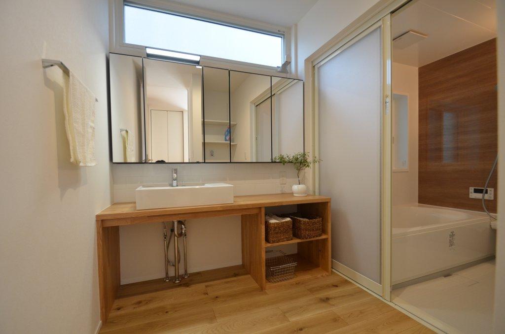 外観のイメージ同様に、インテリアも「白と木」にこだわりデザイン。下がオープンの洗面化粧台は既製品の造作の組み合わせで作り上げた清潔感漂う洗面脱衣室。