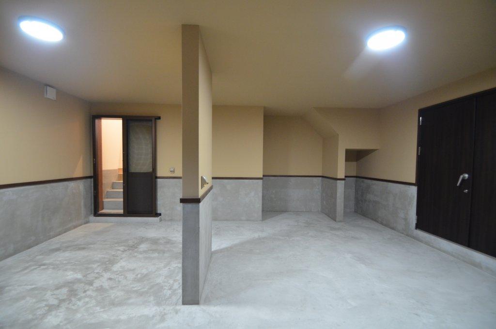 低い道路に面したインナーガレージ。大きな扉を開けると防音室、階段を上って玄関収納へ。
