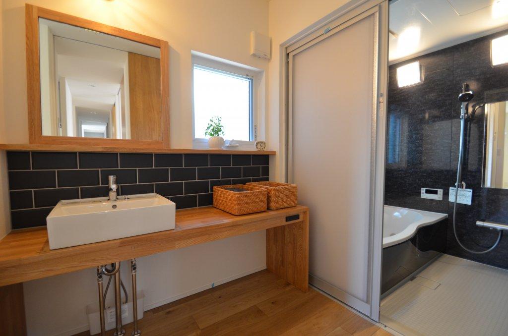 下がオープン、造作の洗面化粧台。水撥ね防止のタイルがアクセント