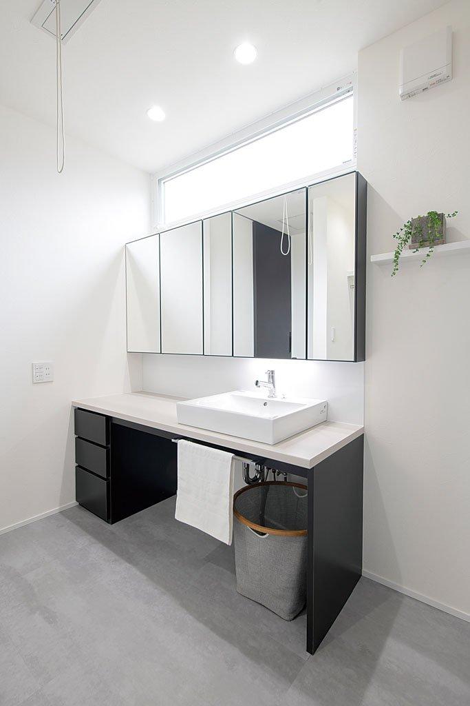 奥様のメークスペースや収納を設けた洗面。ワイドな鏡の裏は収納棚。収納扉を開けば扉が三面鏡の役割も果たす。