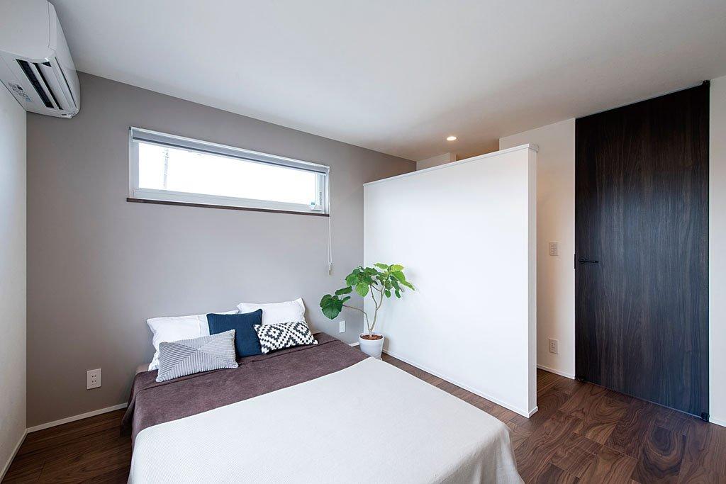 ウオークインクロゼットとの仕切壁の上部に空間をつくることで、部屋全体に広がりをもたらした寝室。