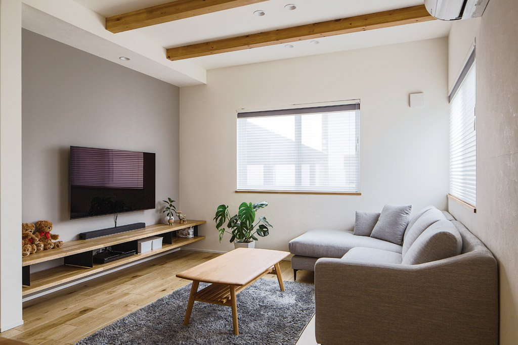 シンプルな造作TVボードは収納力があり掃除もしやすい。グレーのソファやカーペットが空間に溶け込んでいる。