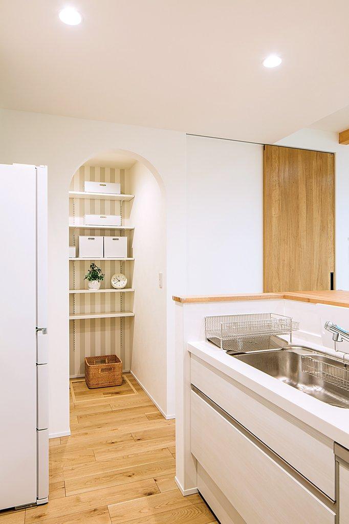 キッチンの隣はアーチ型の垂れ壁がかわいいパントリー。食品や日用品のストックなどはケースに入れて整理整頓。