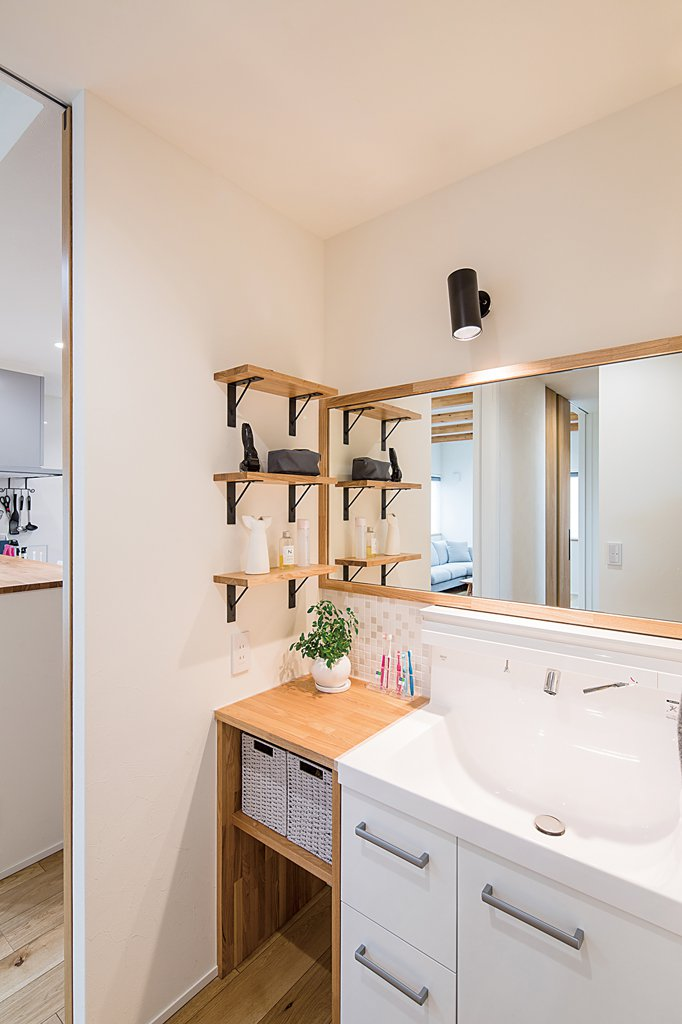 玄関からまっすぐ進んだ場所には洗面スペースが。「洗面台の隣にカウンターを造作していただいたので、2人で並んで使えて便利ですね」(ご主人)。